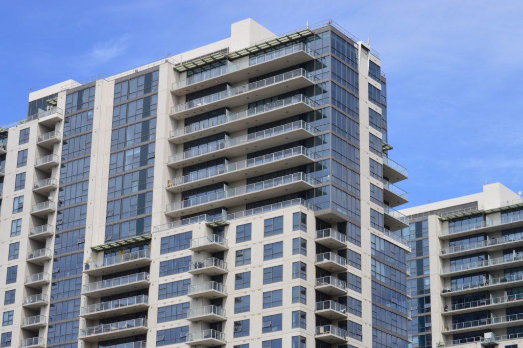 glass concrete condo building blue sky